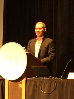 Picture of Neal Cohn, CPSC Small Business Ombudsman, at the 2016 Toy Fair in New York City. discussing the CPSC's Regulatory Robot.